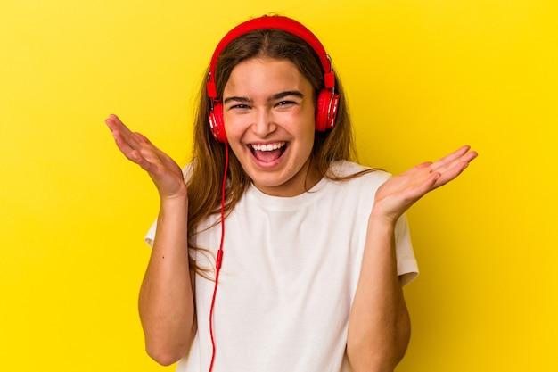 Молодая кавказская женщина слушает музыку, изолированную на желтом фоне, получая приятный сюрприз, взволнованный и поднимающий руки.