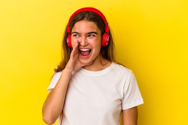 Молодая кавказская женщина слушает музыку, изолированную на желтом фоне, кричит и держит ладонь возле открытого рта.