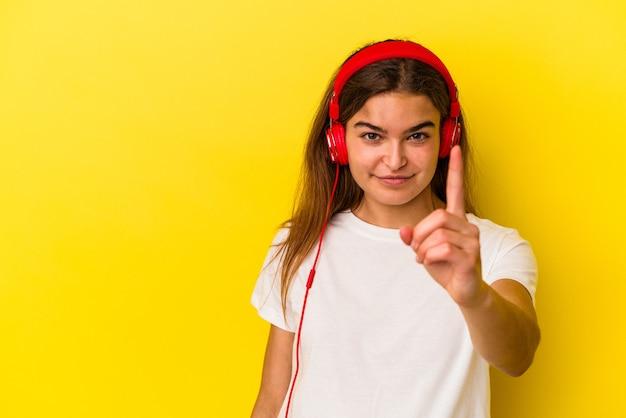 Молодая кавказская женщина, слушающая музыку, изолирована на желтом фоне, показывая номер один пальцем.