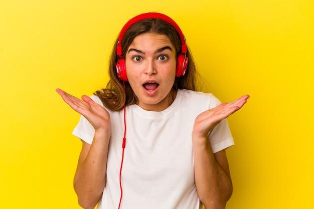Молодая кавказская женщина, слушающая музыку, изолированную на желтом фоне, удивлена и шокирована.