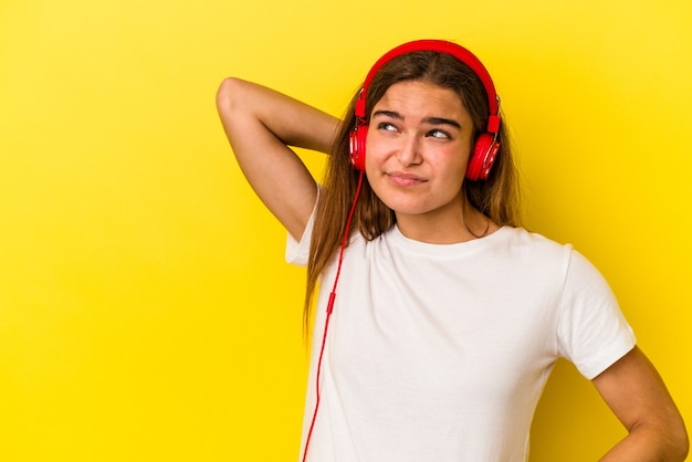 Молодая кавказская женщина слушает музыку, изолированную на желтом фоне, касаясь затылка, думая и делая выбор.