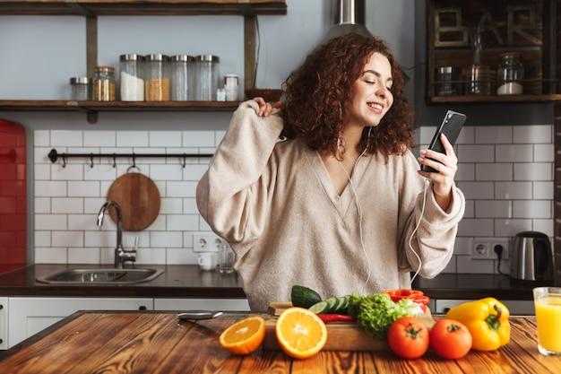 Молодая кавказская женщина слушает музыку на мобильном телефоне во время приготовления салата из свежих овощей в интерьере кухни дома
