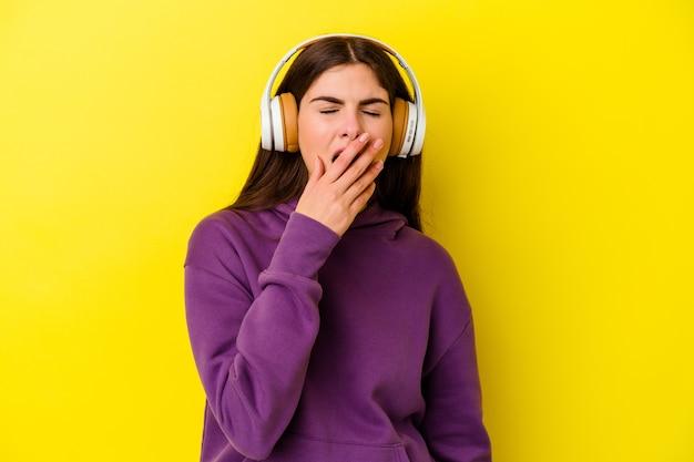 Молодая кавказская женщина слушает музыку с наушниками, изолированными на розовом фоне, зевая, показывая усталый жест, охватывающий рот рукой.