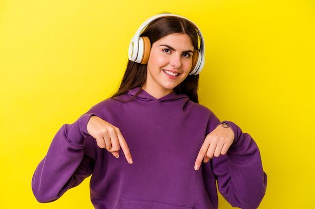 Молодая кавказская женщина, слушающая музыку в наушниках, изолированных на розовой стене, указывает пальцами вниз, положительное чувство.
