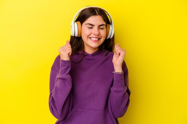 행복하고 성공적인 느낌, 주먹을 올리는 분홍색 벽에 고립 된 헤드폰으로 음악을 듣고 젊은 백인 여자