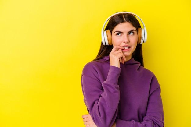 분홍색 벽에 고립 된 헤드폰으로 음악을 듣고 젊은 백인 여자 복사본 공간을보고 뭔가에 대해 생각 편안한