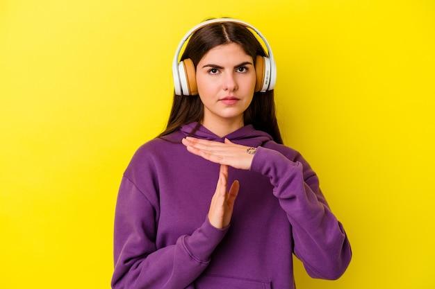 타임 아웃 제스처를 보여주는 분홍색 벽에 고립 된 헤드폰으로 음악을 듣고 젊은 백인 여자