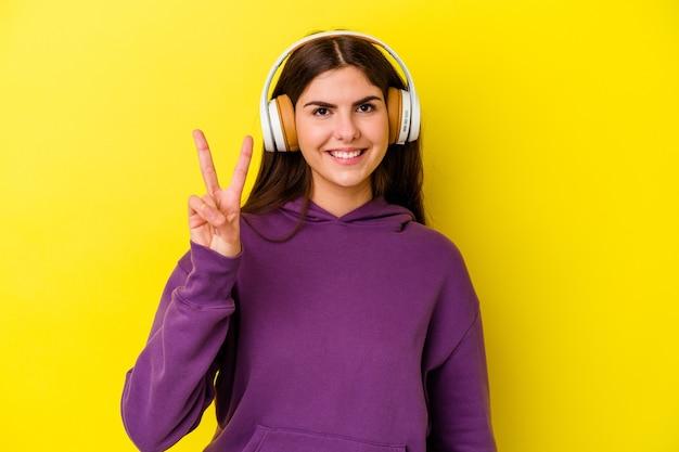 Молодая кавказская женщина слушает музыку с наушниками, изолированными на розовой стене, показывая номер два пальцами.