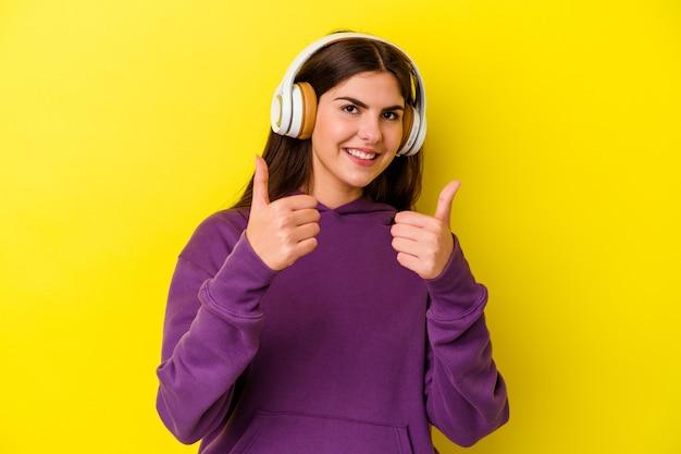 엄지 손가락으로 분홍색 벽에 고립 된 헤드폰으로 음악을 듣고 젊은 백인 여자 ups, 뭔가에 대 한 건배, 지원 및 존중 개념.