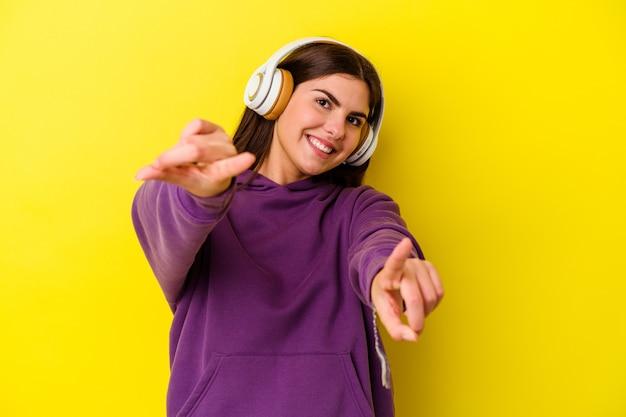 앞을 가리키는 분홍색 밝은 미소에 헤드폰으로 음악을 듣고 젊은 백인 여자.