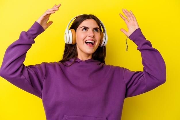 ピンクのヘッドフォンで音楽を聴いている若い白人女性が空に向かって叫び、見上げて、欲求不満。