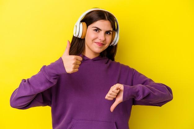 엄지 손가락과 엄지 손가락을 보여주는 분홍색 헤드폰으로 음악을 듣고 젊은 백인 여자, 어려운 개념을 선택