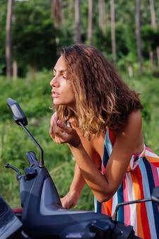 열 대 필드에 오토바이 거울에 젊은 백인 여자 모습