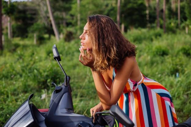 Giovane donna caucasica guarda nello specchio del motociclo sul campo tropicale