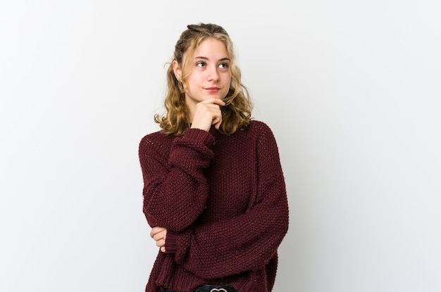 Young caucasian woman looking sideways with doubtful and skeptical expression.