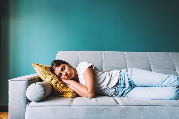 Молодая кавказская женщина, лежа на диване в гостиной, спит после тяжелого рабочего дня