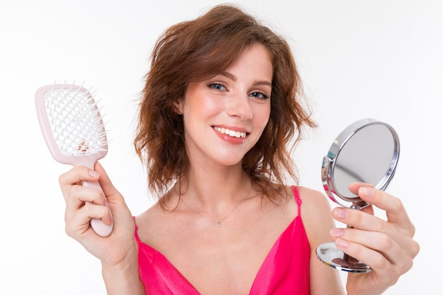 A young caucasian woman do makeup isolated on white background