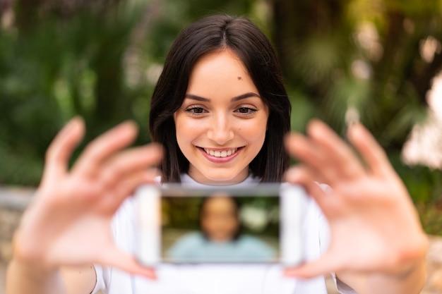 屋外で自分撮りをしている若い白人女性