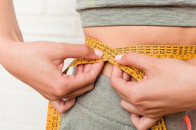 Young caucasian woman measuring her waist