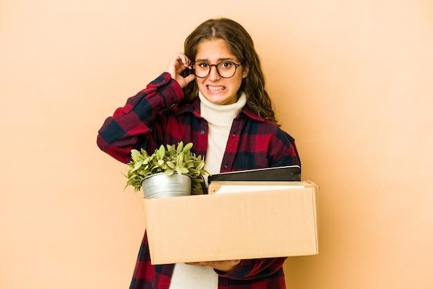 손으로 귀를 덮고 상자를 들고 이동하는 젊은 백인 여자.