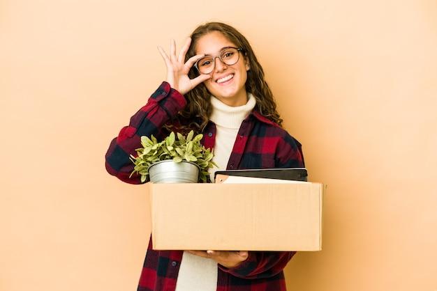 Молодая кавказская женщина, движущаяся, держа коробку, изолировала возбужденное, держа одобренный жест на глазу.