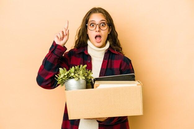アイデア、インスピレーションの概念を持って分離されたボックスを保持して移動する若い白人女性。