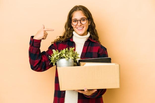 Молодая кавказская женщина движется, держа коробку изолированного человека, указывая рукой на пространство копии рубашки, гордый и уверенный