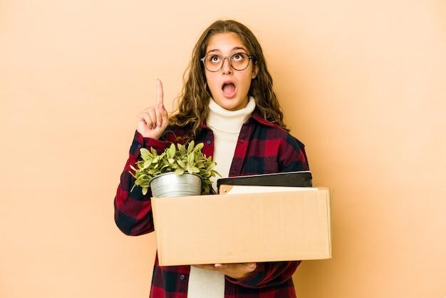 口を開けて逆さまに孤立した箱を持って移動する若い白人女性。