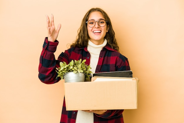 Молодая кавказская женщина движется, держа коробку, изолированную, получая приятный сюрприз, возбужденный и поднимающий руки.