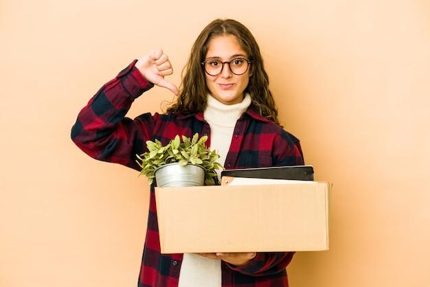 親指を下に向けて、嫌いなジェスチャーを示す孤立したボックスを持って移動する若い白人女性。不一致の概念。