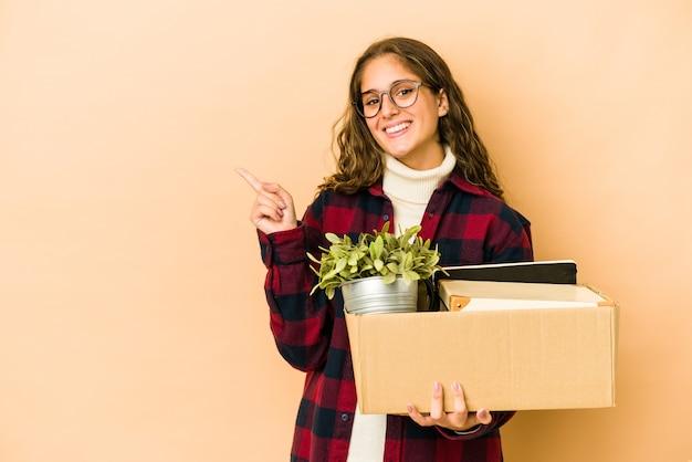 Молодая кавказская женщина движется, держа коробку изолированной, улыбаясь и указывая в сторону, показывая что-то на пустом месте