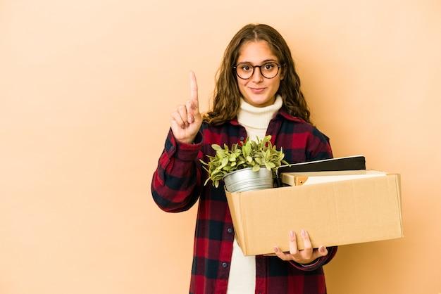 指でナンバーワンを示すボックスを持って移動する若い白人女性。