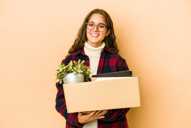 Young caucasian woman moving holding a box isolated laughing and having fun.