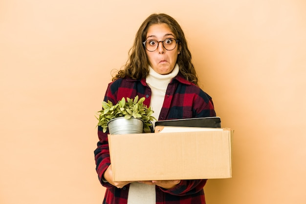 Young caucasian woman moving holding a box isolated shrugs shoulders and open eyes confused.