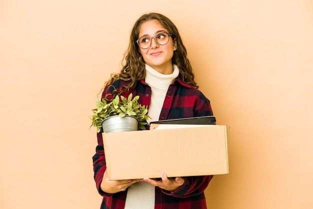 Young caucasian woman moving holding a box isolated