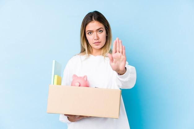 Молодая кавказская женщина, переезжая домой, изолировала положение с протянутой рукой, показывая знак остановки, предотвращая вас.