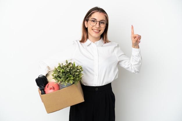 흰색 배경에 고립 된 상자 사이에서 새 집으로 이동하고 최고의 기호에 손가락을 드는 젊은 백인 여자