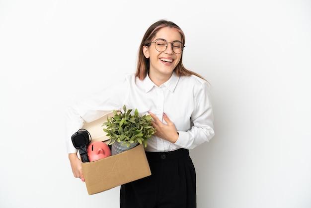 たくさん笑って白い背景で隔離のボックスの中で新しい家に移動する若い白人女性