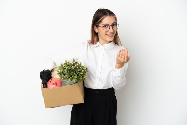 Young caucasian woman moving in new home among boxes isolated on white background inviting to come with hand. happy that you came