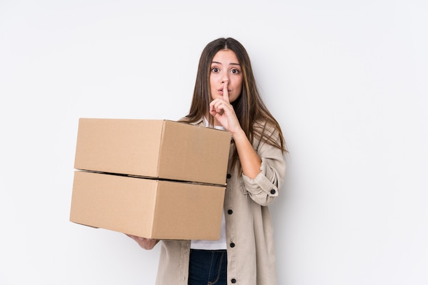 Young caucasian woman moving to a new home keeping a secret or asking for silence.