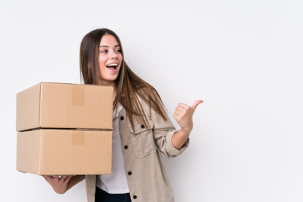 Young caucasian woman moving to a new home points with thumb finger away, laughing and carefree