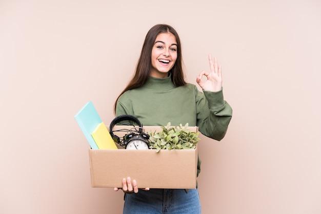新しい家に移動する若い白人女性は、元気で自信を持って大丈夫なジェスチャーを示しています。