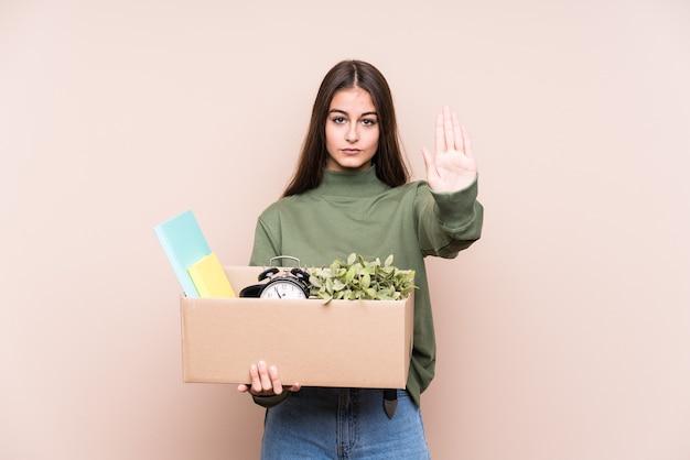 一時停止の標識を示している手を伸ばして孤立した新しい家に移動する若い白人女性は、あなたを防ぎます。