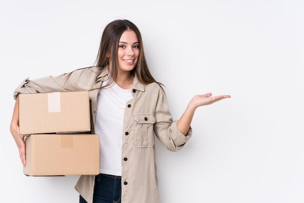手のひらにコピースペースを示し、腰に別の手を握って新しい家に移動する若い白人女性。
