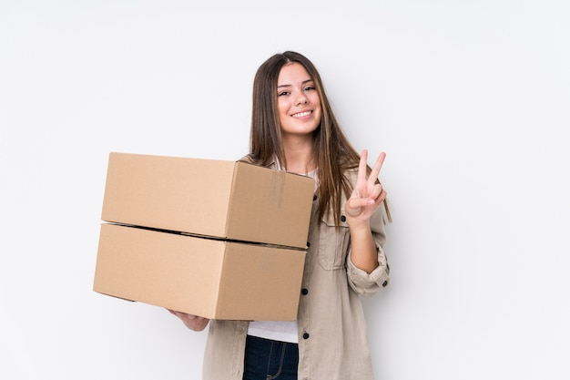 指で2番目を示す新しい家に移動する若い白人女性。