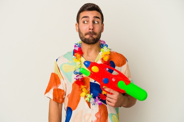 白い背景に隔離された水鉄砲を持っているハワイのパーティーの若い白人女性は混乱し、疑わしくて不安を感じています。