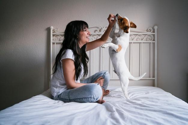 Молодая кавказская женщина на кровати при ее милая маленькая собака играя и давая ему обслуживания. любовь к животным концепции. стиль жизни в помещении