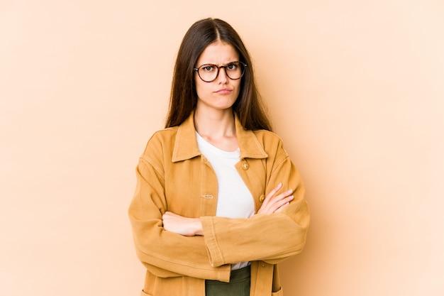 皮肉な表情で見ている不幸なベージュの壁に若い白人女性。