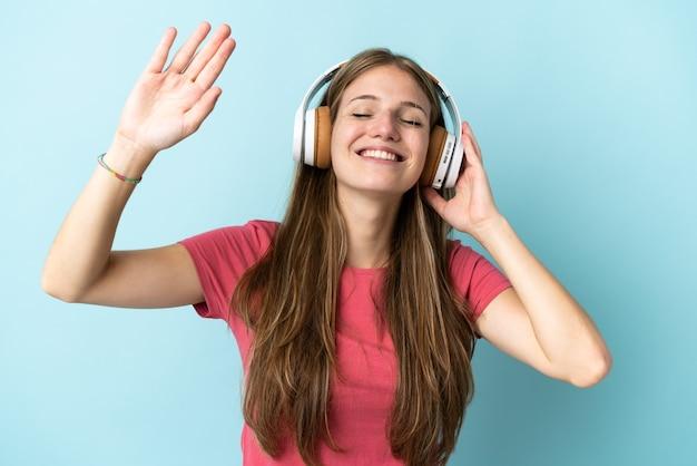 Молодая кавказская женщина на синем прослушивании музыки и танцев