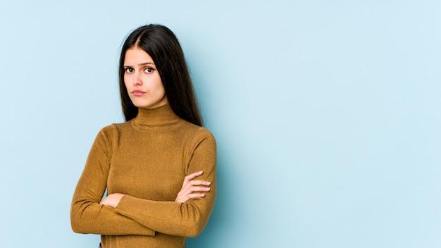 不機嫌そうな表情でカメラで見て不幸な青い壁に若い白人女性。